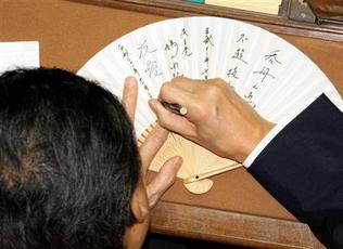 衆院本会議中、扇子にサインをする鳩山由紀夫・首相=26日午後2時25分、国会・衆院本会議場