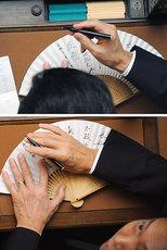 衆院本会議中、扇子に「友愛」「鳩山由紀夫」などと書き込む鳩山由紀夫首相。この後カメラマンの撮影に気づき、扇子を手で覆うしぐさをした=26日午後2時25分、国会・衆院本会議場